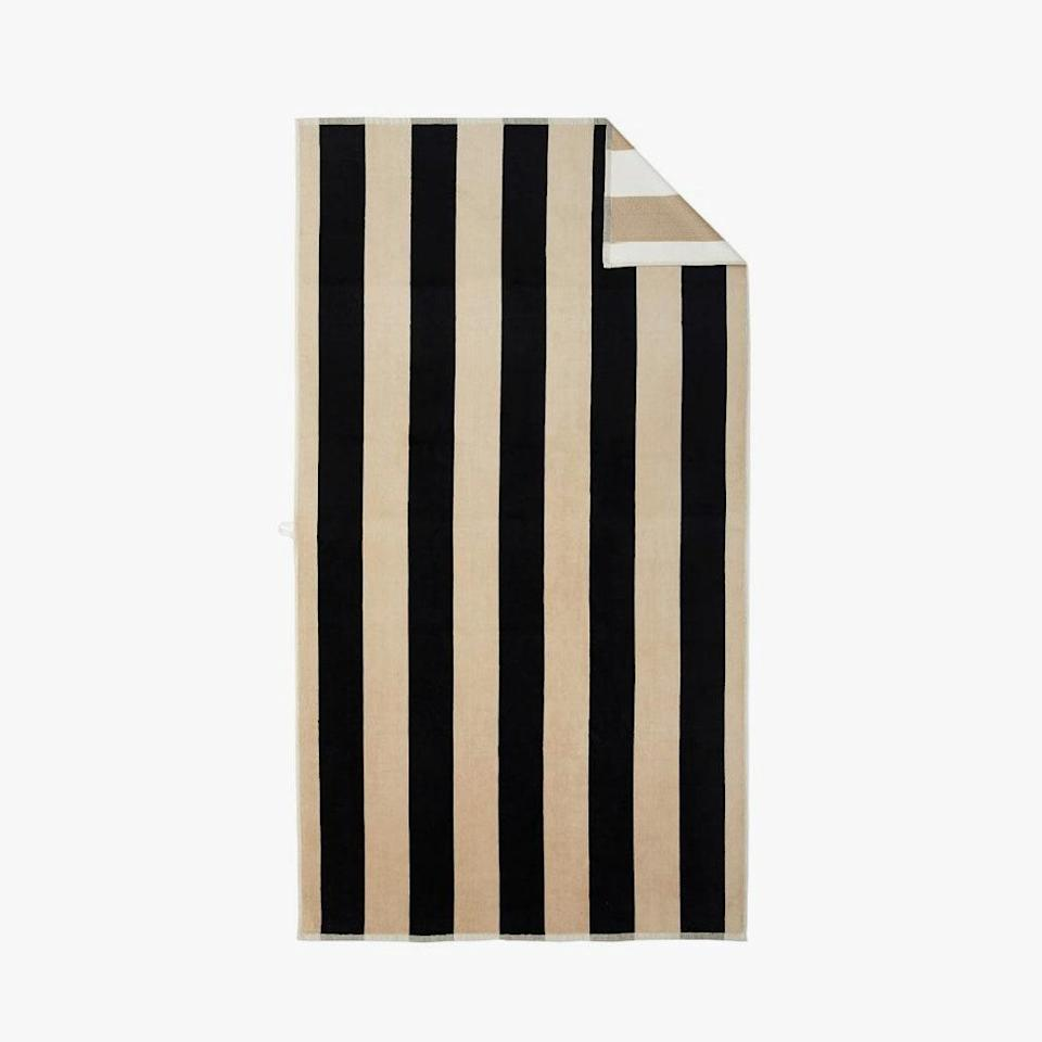 """$50, POTTERY BARN. <a href=""""https://www.potterybarn.com/products/reversible-awning-striped-organic-beach-towel-black-flax/?pkey=cbeach%20towel"""" rel=""""nofollow noopener"""" target=""""_blank"""" data-ylk=""""slk:Get it now!"""" class=""""link rapid-noclick-resp"""">Get it now!</a>"""