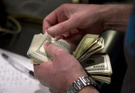 A man counts out $100 bills as he makes a bet on Super Bowl XLVIII at the Las Vegas Hotel & Casino Superbook in Las Vegas, Nevada January 23, 2014. REUTERS/Las Vegas Sun/Steve Marcus