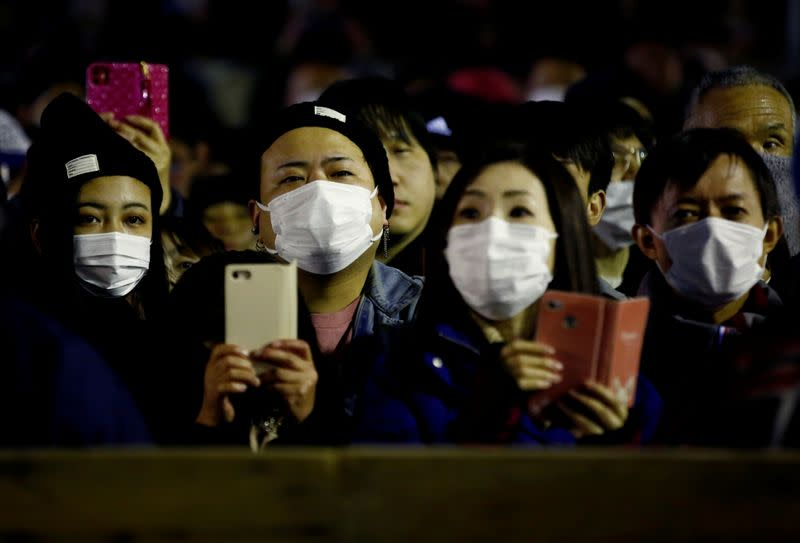 People in protective masks, during the outbreak of the novel coronavirus, watch a naked festival at Saidaiji Temple in Okayama