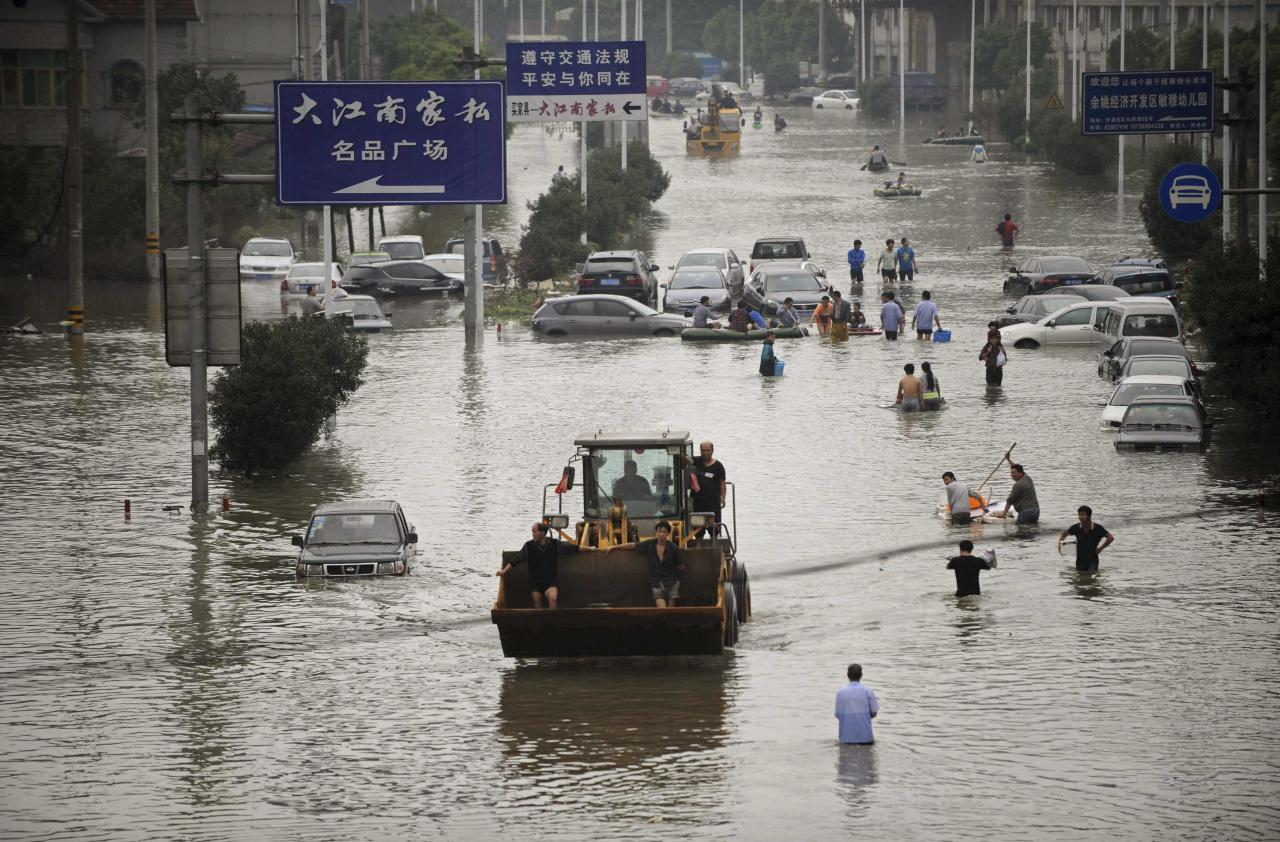 Residents travel on a bulldozer as others walk amid a flooded street after Typhoon Fitow hit Yuyao, Zhejiang province October 9, 2013. Torrential rains caused by Typhoon Fitow continued to lash Shanghai City and Zhejiang Province in eastern China, inundating roads, houses and causing river dike breaches. From Saturday to 10 a.m. Tuesday, Zhejiang saw average precipitation of 201 mm, with 717 mm in worst-hit Yuyao City, Xinhua News Agency reported. REUTERS/Lang Lang (CHINA - Tags: SOCIETY ENVIRONMENT DISASTER)
