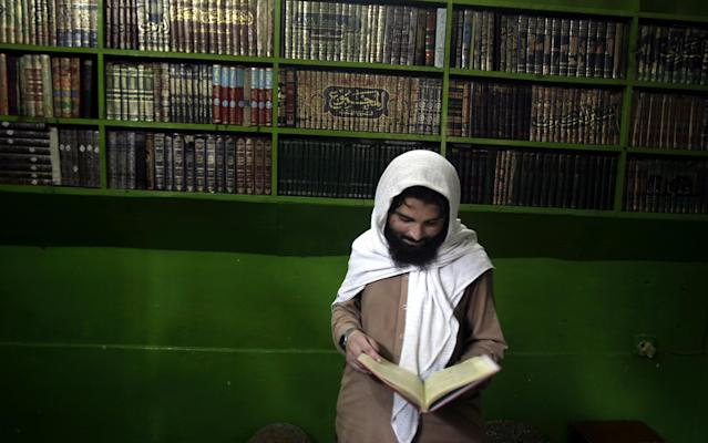 A Pakistani religious student looks at a religious book in the Jamia Taleem-Ul-Quran-Wal-Hadith Madrassa, in Peshawar, Pakistan, Wednesday, Aug. 21, 2013. The United States has placed unprecedented sanctions on an Islamic school in northwest Pakistan for allegedly training and financing fighters from al-Qaida and other militant groups. (AP Photo/Mohammad Sajjad)
