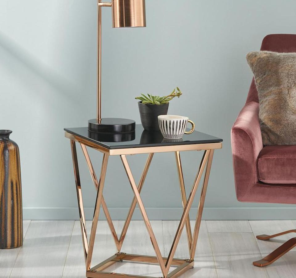 """With ablack glass top and rose gold frame, this side table is sure to stand out. It's justgeometric enough and can hold everything from a lamp to your little succulents. Trust us, it looks a lot more expensive than its pricetag.<a href=""""https://fave.co/3iKFe3T"""" target=""""_blank"""" rel=""""noopener noreferrer"""">Originally $134, get it now for $78 at The Home Depot</a>."""
