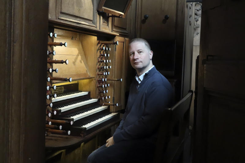 Johann Vexo, the organist who was playing at evening mass inside Notre Dame when flames began licking at the iconic cathedral's roof, poses at the pipe organ at Notre Dame de Nancy cathedral, eastern France, Wednesday, April 17, 2019. Vexo , who was playing at evening mass inside Notre Dame when flames began licking at the iconic cathedral's roof says people didn't immediately react when the fire alarm rang as a priest was reading from the Bible. (AP Photo/Oleg Cetinic)