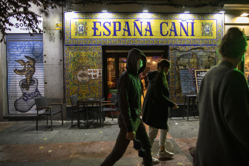MADRID, SPAIN - OCTOBER 25: People walk past a restaurant on the first night of a countrywide curfew on October 25, 2020 in Madrid, Spain. Spain has declared a national state of emergency and imposed a night-time curfew from 11pm to 6am in an effort to help control a new spike in coronavirus (COVID-19) infections. (Photo by Pablo Blazquez Dominguez/Getty Images)