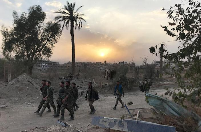 Syrian government forces walk in a district of Deir Ezzor on November 5, 2017, after retaking the city from the Islamic State group but jihadists still hold several villages in the province (AFP Photo/STRINGER)