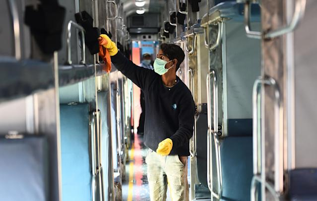 Workers wash and disinfect trains coaches at a rail yard, as a measure to prevent the spread of coronavirus in New Delhi