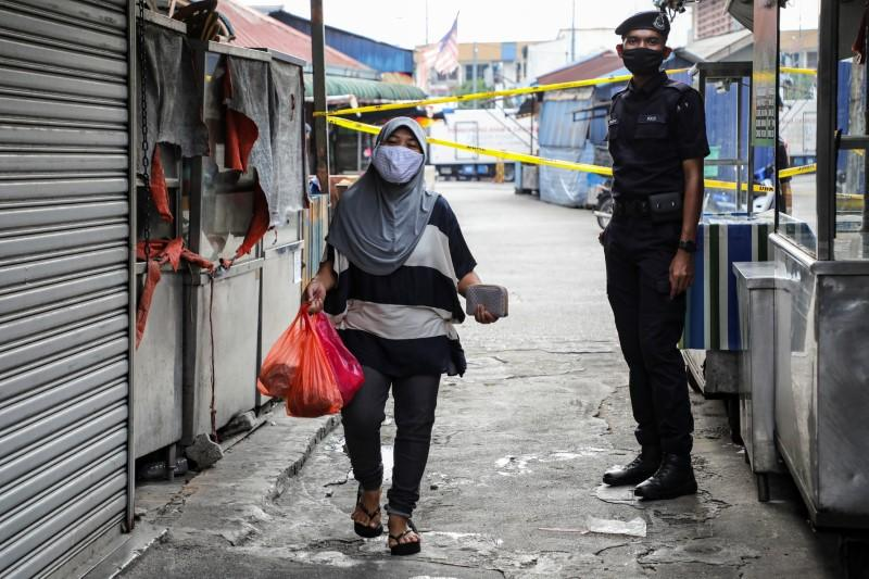 A police officer stands guard at an entrance of a market, during the movement control order due to the outbreak of the coronavirus disease (COVID-19), in Kuala Lumpur