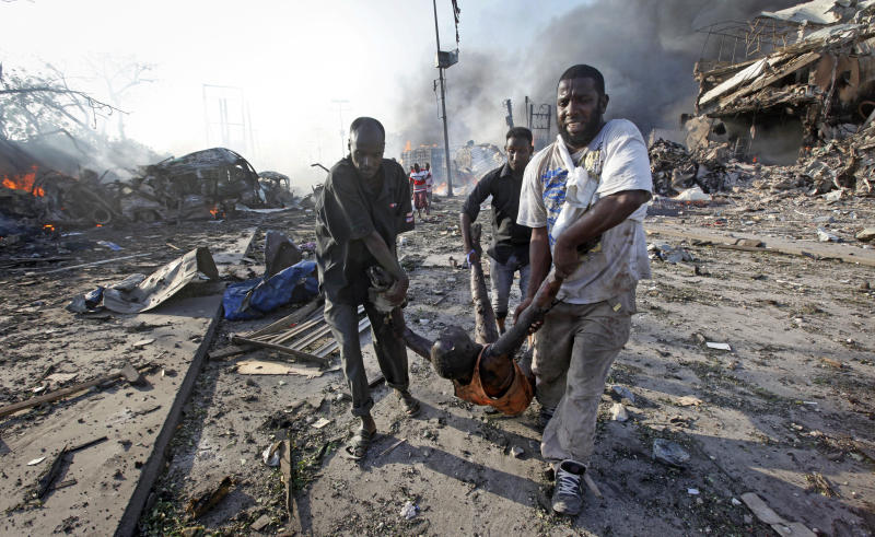 """FILE - In this Saturday, Oct. 14, 2017 file photo, Somalis remove the body of a man killed in a huge explosion from a truck bomb that killed at least 20 people, in the capital Mogadishu, Somalia. U.N. experts said in a report circulated Tuesday, Nov. 12, 2019 that al-Shabab extremists in Somalia remain """"a potent threat"""" to regional peace and are manufacturing home-made explosives, expanding their revenue sources and infiltrating government institutions. (AP Photo/Farah Abdi Warsameh, File)"""