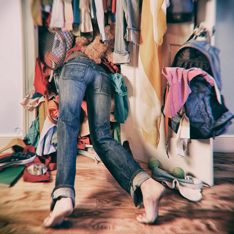 Woman searching in messy closet.