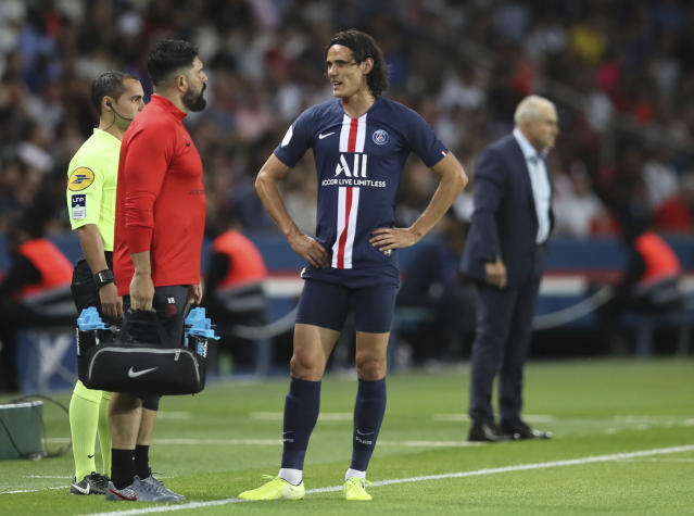 PSG's Edinson Cavani talks to member of medical staff after being injured during the French League One soccer match between Paris Saint Germain and Toulouse at the Parc des Princes Stadium in Paris, France, on Sunday, Aug. 25, 2019. (AP Photo/David Vincent)