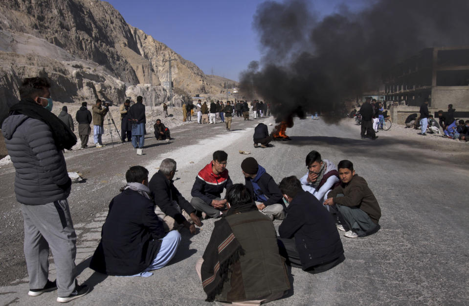 People from the Shiite Hazara community burn tires and block a road in protest of the killing of coal mine workers by unknown gunmen near the Machh coal field, in Quetta, Pakistan, Sunday, Jan. 3, 2021. Gunmen opened fire on a group of minority Shiite Hazara coal miners after abducting them, killing 11 in southwestern Baluchistan province early Sunday, a Pakistani official said. (AP Photo/Arshad Butt)