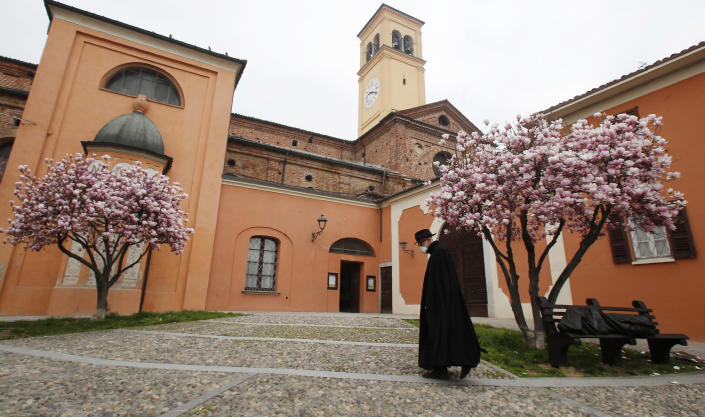 In this photo taken on Thursday, March 12, 2020, a priest wearing a mask walks in Codogno, Italy. The northern Italian town that recorded Italy's first coronavirus infection has offered a virtuous example to fellow Italians, now facing an unprecedented nationwide lockdown, that by staying home, trends can reverse. Infections of the new virus have not stopped in Codogno, which still has registered the most of any of the 10 Lombardy towns Italy's original red zone, but they have slowed. For most people, the new coronavirus causes only mild or moderate symptoms. For some it can cause more severe illness. (AP Photo/Antonio Calanni)
