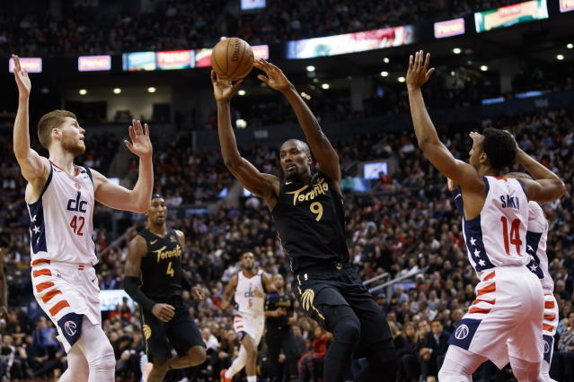Toronto Raptors forward Serge Ibaka (9) looks to make a pass as he's defended by Washington Wizards forward Davis Bertans (42) and guard Ish Smith (14) during the first half of an NBA basketball game Friday, Jan. 17, 2020, in Toronto. (Cole Burston/The Canadian Press via AP)