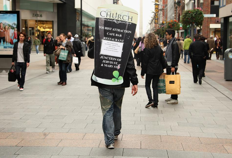 A man with an advertising hoarding on his back walks down the street in Dublin, Ireland.
