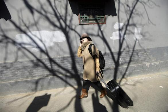 Ms. Zhuang, a Hotel Test Sleeper, uses her mobile phone as she looks for a boutique hotel along a traditional alleyway, or Hutong, in central Beijing March 6, 2012.