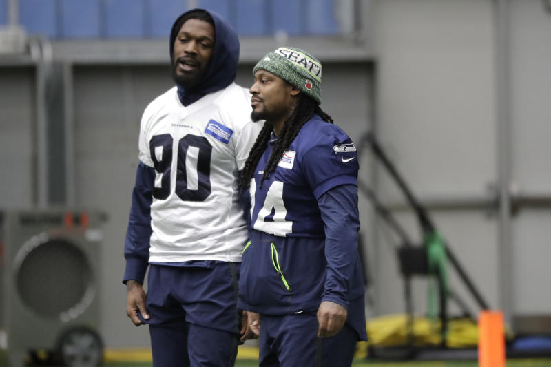 Seattle Seahawks running back Marshawn Lynch, right, talks with defensive end Jadeveon Clowney, left, before NFL football practice, Friday, Dec. 27, 2019, in Renton, Wash. (AP Photo/Ted S. Warren)