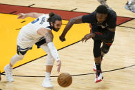 Minnesota Timberwolves guard Ricky Rubio (9) and Miami Heat center Bam Adebayo (13) battle for the ball during the first half of an NBA basketball game, Friday, May 7, 2021, in Miami. (AP Photo/Wilfredo Lee)
