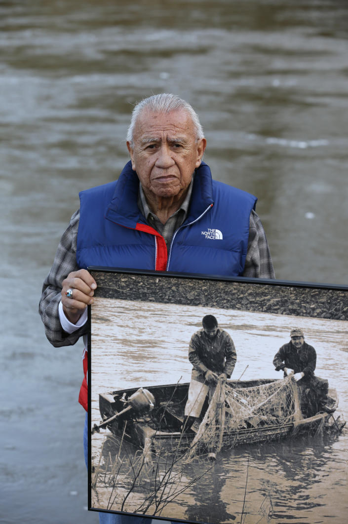 FILE - In this Monday, Jan. 13, 2014, file photo Billy Frank Jr., a Nisqually tribal elder who was arrested dozens of times while trying to assert his native fishing rights during the Fish Wars of the 1960s and '70s, poses for a photo while holding a late 1960s photo of himself, left, fishing with Don McCloud, near Frank's Landing on the Nisqually River in Nisqually, Wash. Gov. Jay Inslee on Wednesday, April 14, 2021, signed a measure that starts the process of honoring the late Frank, who championed treaty rights and protecting the environment with a statue at the U.S. Capitol. (AP Photo/Ted S. Warren, File)