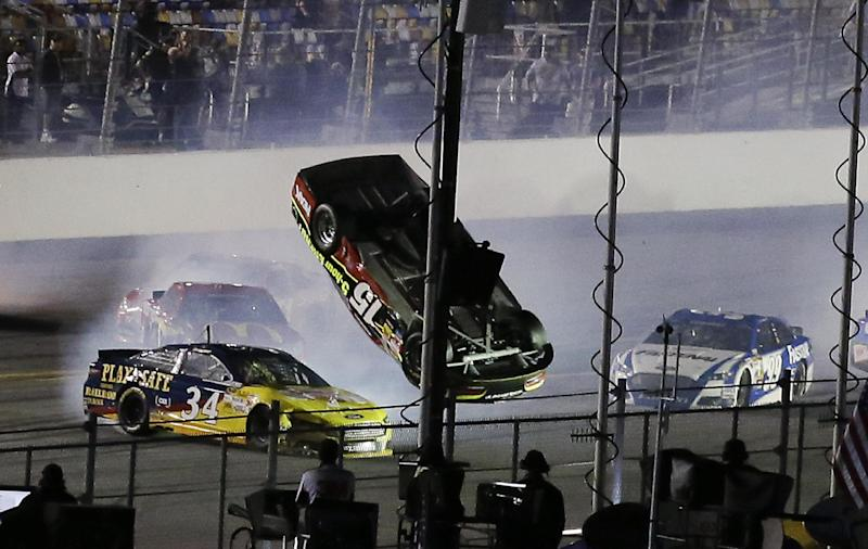 Clint Bowyer (15) flips upside down as he is involved in a multi-car crash with David Ragan (34), Carl Edwards (99) and others on the final lap of the second of two NASCAR Sprint Cup qualifying auto races at Daytona International Speedway in Daytona Beach, Fla., Thursday, Feb. 20, 2014. (AP Photo/John Raoux)