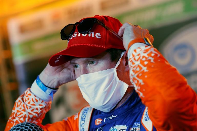 Scott Dixon adjusts his protective mask in victory lane after grabbing the checkered flag in the first IndyCar race in eight months due to the COVID-19 pandemic (AFP Photo/TOM PENNINGTON)