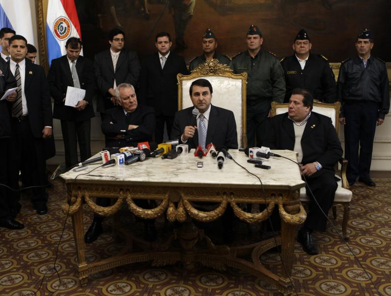 Paraguay's new President Federico Franco, sitting center, gives a news conference at the presidential palace in Asuncion, Paraguay, Saturday, June 23, 2012. Paraguay's newly sworn in president is promising to honor foreign commitments and reach out to Latin American leaders after the Senate removed President Fernando Lugo from office in a rapid impeachment trial on Friday. (AP Photo/Jorge Saenz)