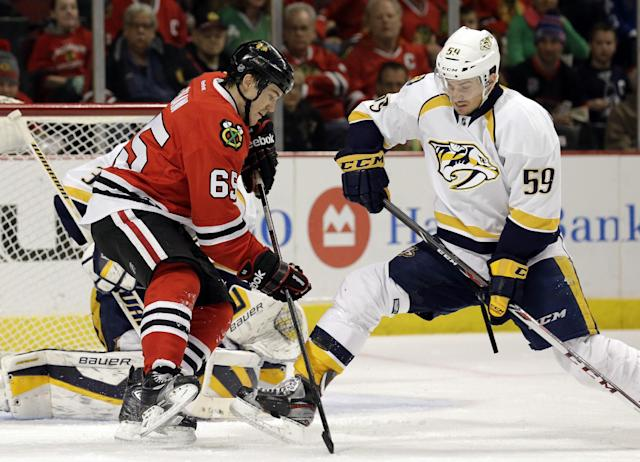 Chicago Blackhawks' Andrew Shaw (65), left, controls the puck against Nashville Predators' Roman Josi (59) during the second period of an NHL hockey game in Chicago, Friday, March 14, 2014. The Predators won 3-2. (AP Photo/Nam Y. Huh)