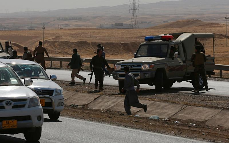 Kurdish security forces withdraw from a checkpoint in Alton Kupri, on the outskirts of Erbil - AP
