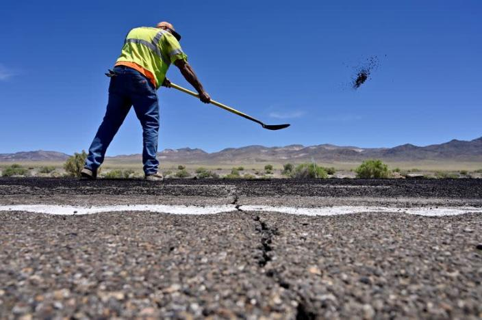 FILE PHOTO: A crack across the roadway is seen as Nevada Department of Transportation worker Jarrid Summerfelt repairs damage to U.S. Highway 95 after a strong earthquake struck near Tonopah