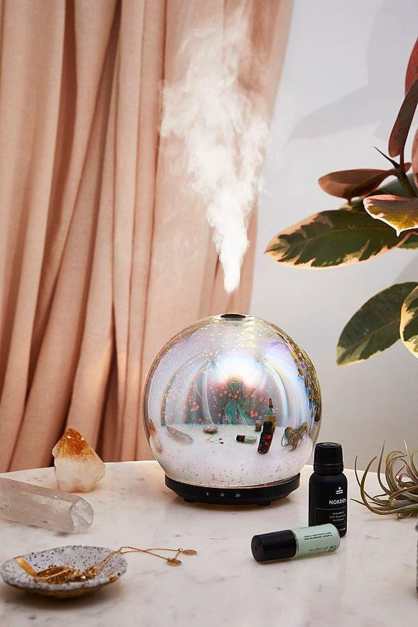 """<p>This <a href=""""https://www.popsugar.com/buy/3D-LED-Gala-Essential-Oil-Diffuser-367670?p_name=3D%20LED%20Gala%20Essential%20Oil%20Diffuser&retailer=urbanoutfitters.com&pid=367670&price=65&evar1=savvy%3Aus&evar9=45342302&evar98=https%3A%2F%2Fwww.popsugar.com%2Fphoto-gallery%2F45342302%2Fimage%2F45342669%2F3D-LED-Gala-Essential-Oil-Diffuser&list1=shopping%2Cgifts%2Choliday%2Cchristmas%2Cgift%20guide%2Cvalentines%20day%2Cgifts%20for%20women&prop13=api&pdata=1"""" rel=""""nofollow"""" data-shoppable-link=""""1"""" target=""""_blank"""" class=""""ga-track"""" data-ga-category=""""Related"""" data-ga-label=""""https://www.urbanoutfitters.com/shop/3d-led-gala-essential-oil-diffuser?category=best-music-tech&amp;color=095"""" data-ga-action=""""In-Line Links"""">3D LED Gala Essential Oil Diffuser</a> ($65) is downright magical.</p>"""
