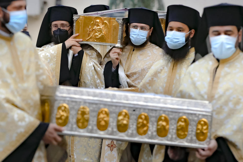 Priests, wearing masks against the COVID-19 infection, carry the remains of Saint Dimitrie Bassarabov, the patron saint of the Romanian capital, on the first of three days of pilgrimage, taking place at a much smaller scale than usual, due to the pandemic control imposed measures, in Bucharest, Romania, Sunday, Oct. 25, 2020. Romania's daily tally of coronavirus infections rose above 5,000 for the first time last week and patients in intensive care units also reached a new high. (AP Photo/Vadim Ghirda)