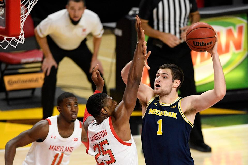 Michigan center Hunter Dickinson (1) goes to the basket next to Maryland forward Jairus Hamilton (25) and guard Darryl Morsell (11) during the first half of an NCAA college basketball game, Thursday, Dec. 31, 2020, in College Park, Md.