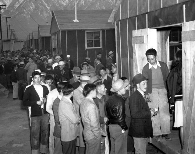 Japanese citizens wait in line for their assigned homes at an internment camp reception center in Manzanar, Calif., on March 24, 1942. Many were forced from their homes in Los Angeles by the U.S. Army. (AP)