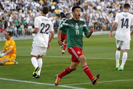Mexico's Peralta celebrates after scoring a goal as New Zealand's Moss, Durante and Roux react during their 2014 World Cup qualifying playoff second leg soccer match in Wellington