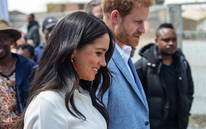 """(FILES) In this file photo taken on October 02, 2019 Britain's Prince Harry, Duke of Sussex(R) and Meghan, Duchess of Sussex(L) leave the Youth Employment Services Hub in Tembisa township, Johannesburg. - Meghan Markle is to release a children's book titled """"The Bench"""" inspired by her husband Prince Harry's bond with their son Archie, the couple's foundation announced May 4, 2021. - Michele Spatari/AFP via Getty Images"""
