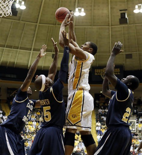 Southern Mississippi forward Daveon Boardingham, second from right, shoots a basket over the defense of Charleston Southern forward Paul Gombwer (15) in the first half of their NIT college basketball game in Hattiesburg, Miss., Wednesday, March 20, 2013. (AP Photo/Rogelio V. Solis)