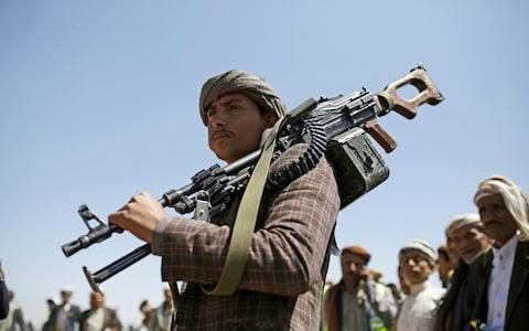 A Shiite Houthi tribesman holds his weapon during a tribal gathering showing support for the Houthi movement, in Sanaa, Yemen - Credit: AP