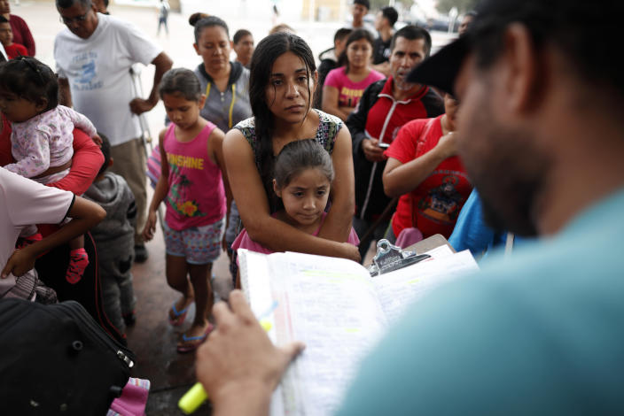 A Mexican woman embraces her daughter as names are read from a list of people who will cross into the U.S. to begin the process of applying for asylum in July 2018 near the San Ysidro Port of Entry in Tijuana, Mexico. (Photo: Gregory Bull/AP)