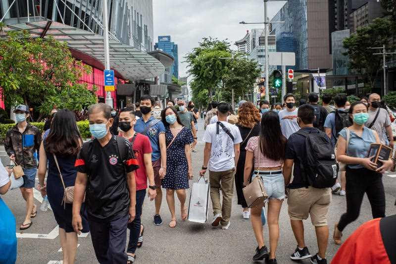 People wearing face masks as a preventive measure against the spread of covid-19 walk along Orchard Road, a famous shopping district in Singapore