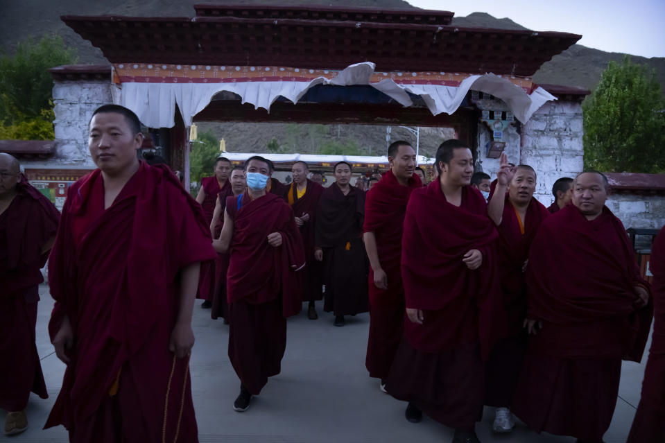 Monks prepare to go to dinner at the Tibetan Buddhist College near Lhasa in western China's Tibet Autonomous Region, Monday, May 31, 2021, as seen during a government organized visit for foreign journalists. High-pressure tactics employed by China's ruling Communist Party appear to be finding success in separating Tibetans from their traditional Buddhist culture and the influence of the Dalai Lama. (AP Photo/Mark Schiefelbein)
