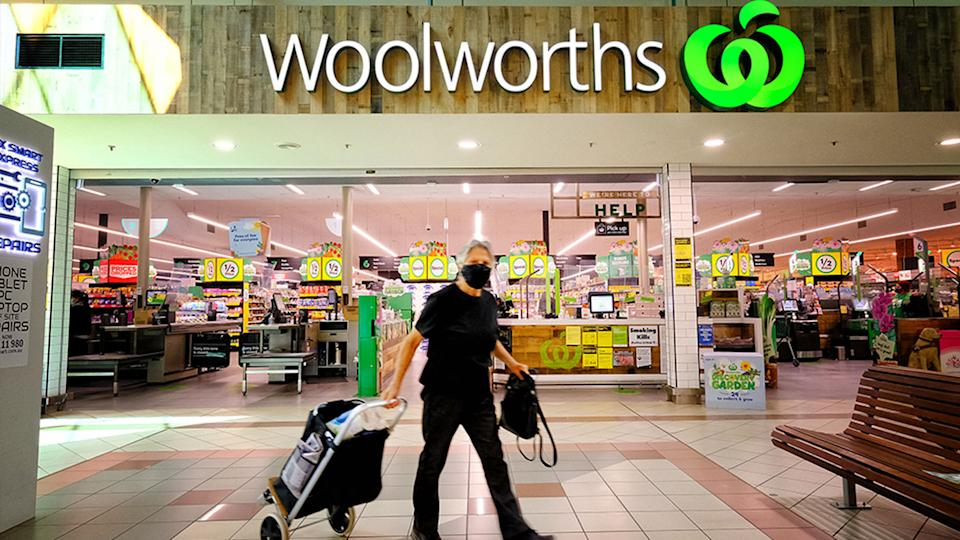 Pictured is the outside of a Woolworths supermarket, with a man wearing a mask walking outside.