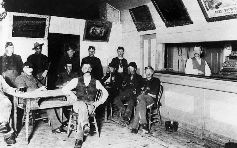 <p>Men sit in a canteen at Fort Keogh, Montana. The city is a former Army post. Some of the men at the canteen can be seen wearing military uniforms.</p>