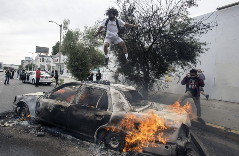 Pictured is a man jumping on a burning police car in LA. Source: AP