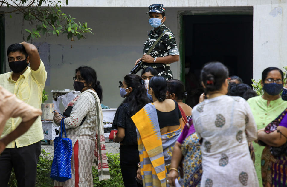 A paramilitary solder stands vigil as people stand in a queue to cast their votes outside a polling station during the fourth phase of West Bengal state elections in Kolkata, India, Saturday, April 10, 2021. (AP Photo/Bikas Das)