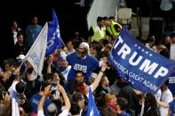 FILE PHOTO: A supporter of Israeli Prime Minister Netanyahu's Likud party waves flags, one bearing the name of U.S. President Trump, as the crowd reacts to exit polls in Israel's parliamentary election at the party headquarters in Tel Aviv