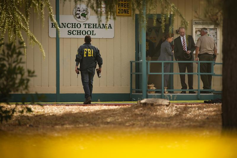 FBI agents are seen behind yellow crime scene tape outside Rancho Tehama Elementary School, one of several locations targeted by a gunman in California in November 2017