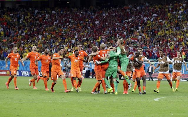 The Dutch team celebrates after the Netherlands defeated Costa Rica 4-3 in a penalty shootout after a 0-0 tie during the World Cup quarterfinal soccer match at the Arena Fonte Nova in Salvador, Brazil, Saturday, July 5, 2014. (AP Photo/Wong Maye-E)