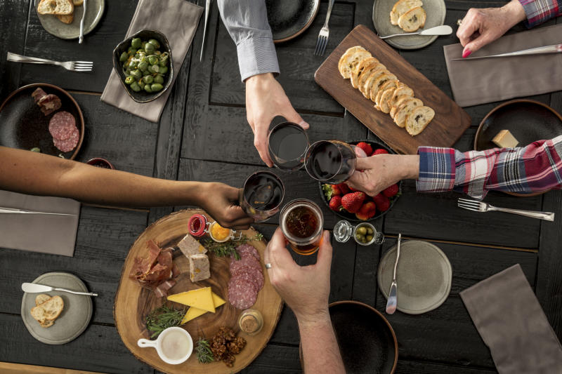 Friends sharing charcuterie and tapas with wine and beer