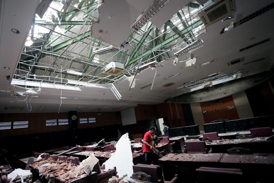 <p>A man cleans up a damaged courtroom affected by an earthquake of magnitude 5.9 struck in the ocean 91 km (57 miles) south-southeast of Blitar</p> (Via REUTERS)