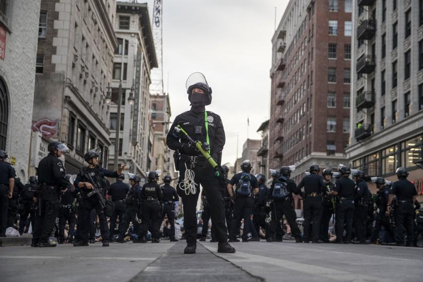 Los Angeles, CA, Tuesday, June 2, 2020 - LAPD officer Decote watches for people tossing debris from tall buildings as dozens of protesters are arrested for curfew violations on Broadway. (Robert Gauthier / Los Angeles Times)