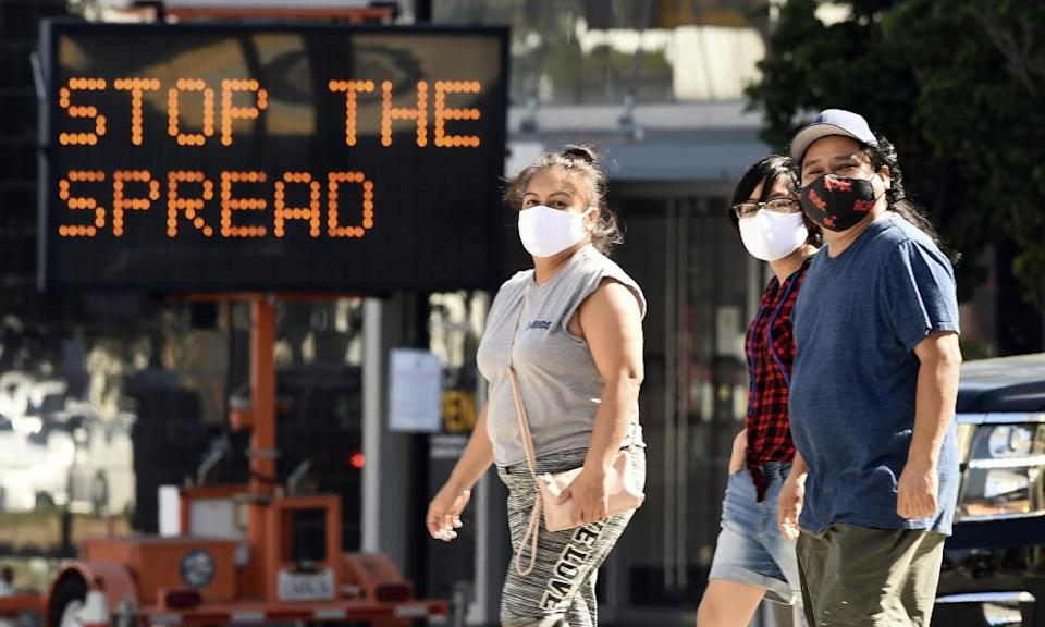 People wearing masks in front of a coronavirus sign urging citizens to 'stop the spread'.